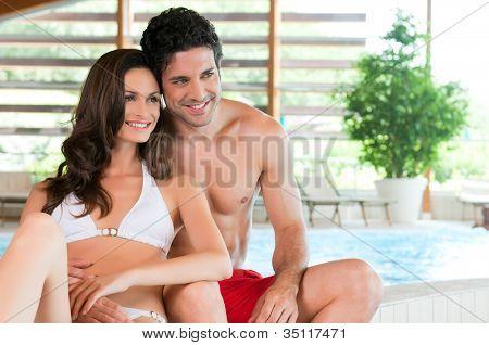 Hermosa joven pareja relajarse juntos en el borde de una piscina en el centro de spa