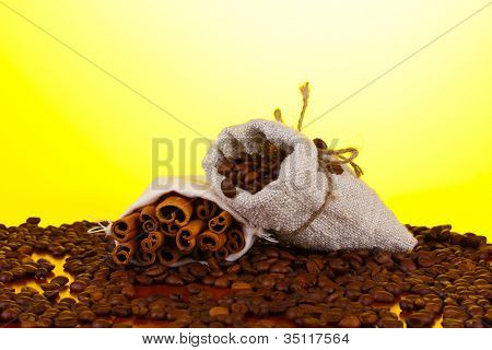Coffee beans is poured out of the canvas sack on yellow background