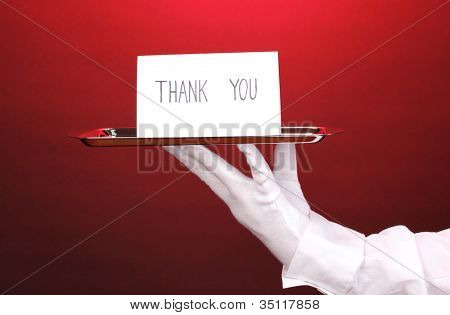Hand in glove holding silver tray with card saying thank you on red background