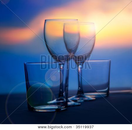 Dish of cups and crystal transparent glasses on a sea sunset table