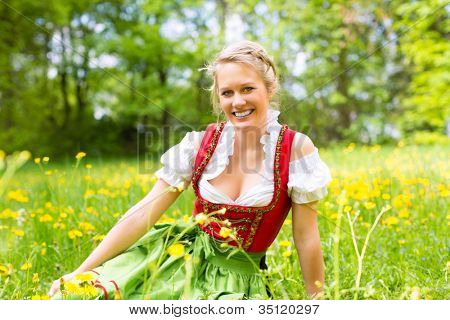 Young woman in traditional Bavarian clothes - dirndl or tracht - on a meadow in spring