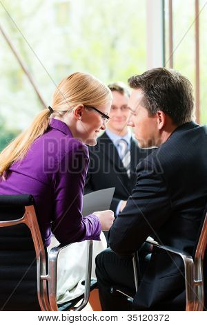 Business - young man as applicant sitting in job interview with future boss and HR