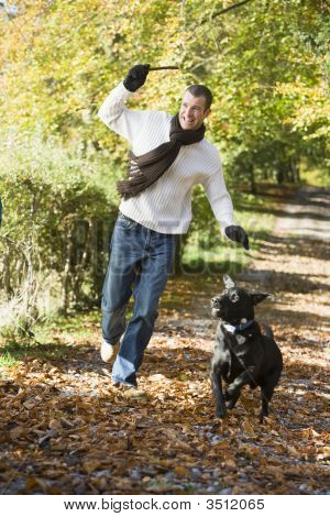 Man Outdoors With Dog On Path In Park Holding Branch Smiling