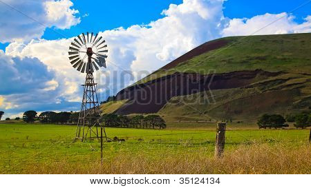 Windmill on a farmland fence with volcanic mountain in the background