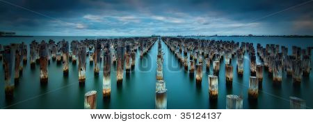Old Pier Stumps in the blue sea water of Port Melbourne, Australia