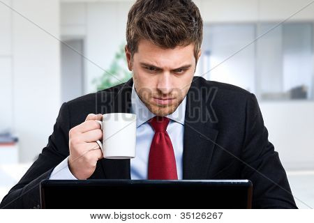 Businessman using his computer while drinking coffee