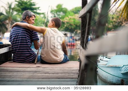 Old Man And Boy Fishing Together On River For Fun