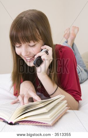 Teenager Lying On Bed Reading And Book And Talking On A Mobile Phone
