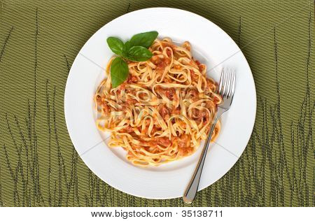 linguini pasta with tomato sauce overhead on white plate