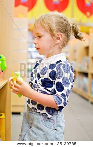 Little Girl Is Shopping At The Children's Store.