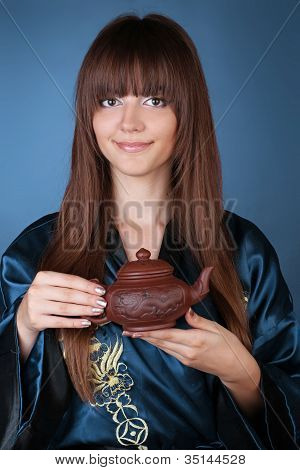Tea Ceremony Woman With Long Brown Hair, Teapot On Hands Over Blue