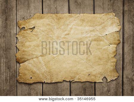 Old Paper At Grunge Wooden Background