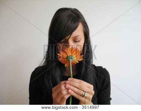 dunkles Haar Mädchen riechen eine Blume