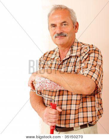 Alter Mann mit Farbroller