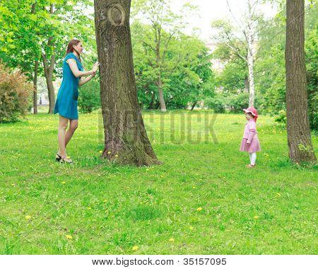 Mutter und Mädchen spielen verstecken und suchen