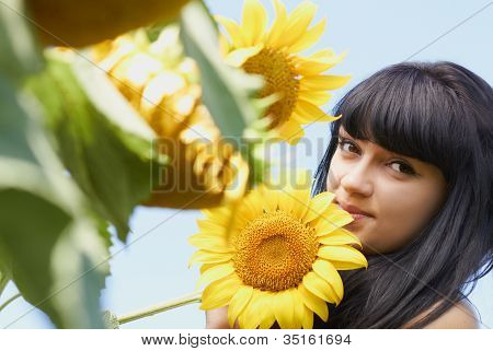 Girl With Sunflower Under Blue Sky