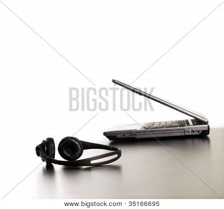 Modern Computer And Headphones In A Row.