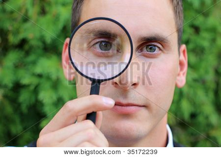 Man Looking Through Magnifying Glass While Serious