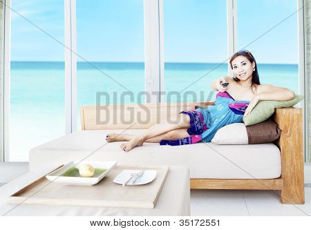 Asian Woman Watching Tv By The Beach