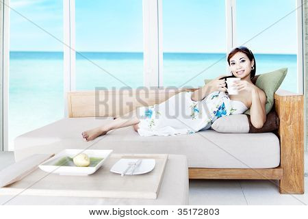 Woman Having Tea In Beach Apartment