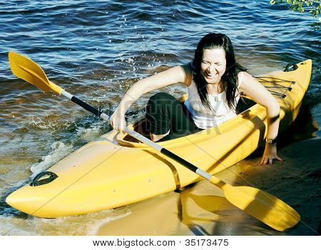 Cute girl in a yellow kayak