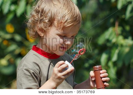 Little blond boy playing with bubbles outdoors on a sunny day
