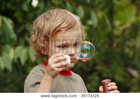 Little blond boy playing with bubbles