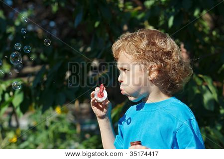 Little blond boy blowing a bubbles outdoors on a sunny day