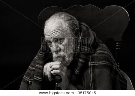 Sad old man sitting alone lost in thought