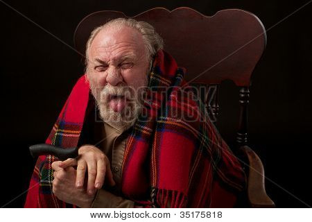 Grumpy old man with shawl and cane sticks out tongue