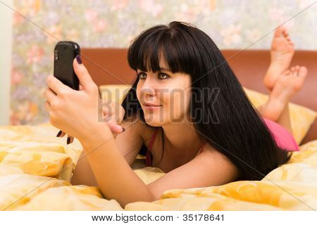 Smiling Young Woman With Mobile Phone In Bed