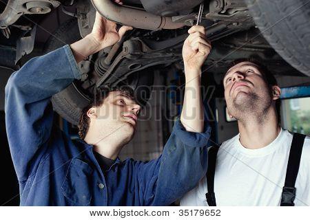 Two Car Mechanic Repairing Car