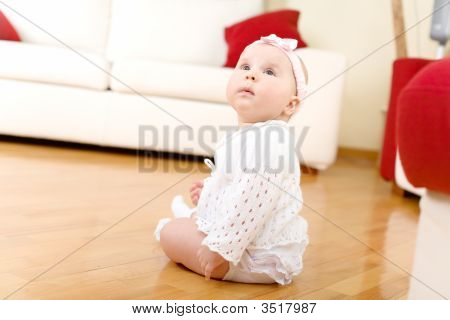 Baby Girl Seated On A Hardwood Floor