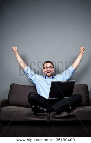Businessman With Laptop Raises Arms