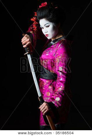Portrait Of Geisha Warrior Pulls Out Sword Of Sheath On Black