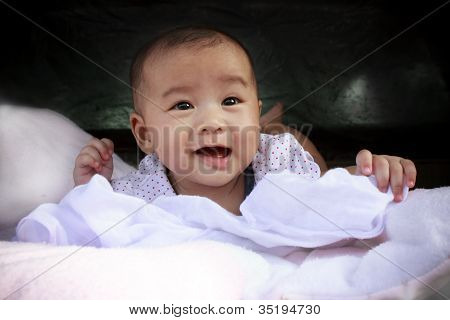 asian baby smiling face lied on bed