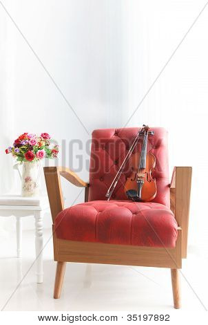 red leather wood arm chair with violin in white room