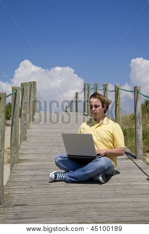 young man working with computer at the beach