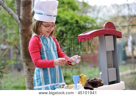 little girl playing cooking in garden
