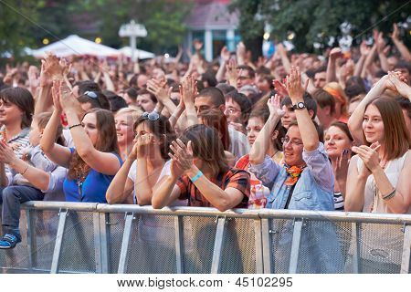 MOSCOW - JUN 23: Music fans applaud at concert of Chaif rock-band during VII traditional festival of live sound Music of Summer in Hermitage Garden, Jun 23, 2012, Moscow, Russia.