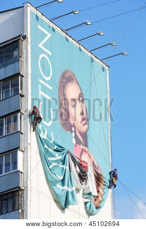 MOSCOW - MAY 16: Workers remove billboard from house, on May 16, 2012 in Moscow, Russia. Moscow does not stop work on dismantling illegally installed outdoor advertising.