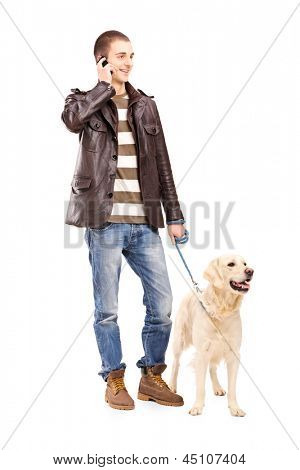 Full length portrait of a young man walking a dog and talking on a mobile phone, isolated on white background