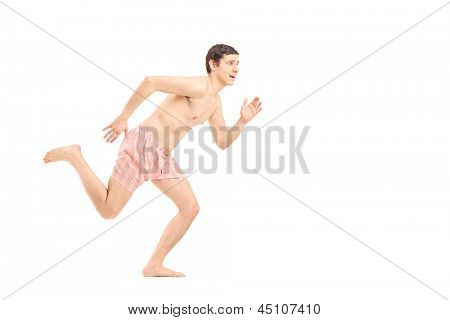 An embarrassed naked man in underwear running away, isolated on white background