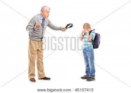 Full length portrait of an angry grandfather holding a belt and threatening on his nephew isolated on white background