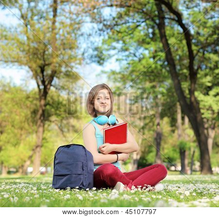 A beautiful young female student with book and headphones sitting on a grass in a park