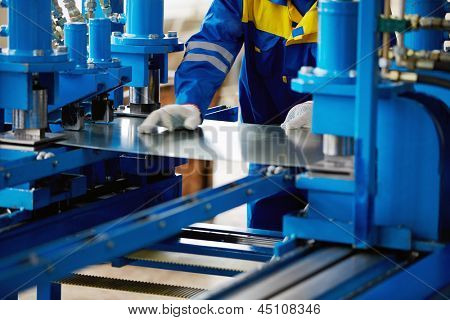 Sheet of metal and hands of worker who works on press