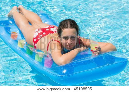 Woman swimming in the pool on an inflatable mattress with a drink in hand
