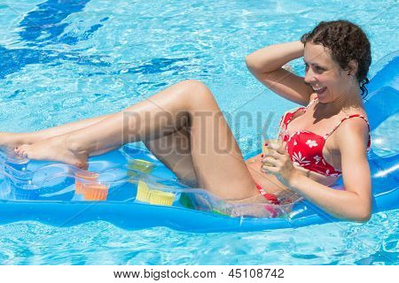 Smiling woman swimming in the pool on an inflatable mattress with a drink in hand