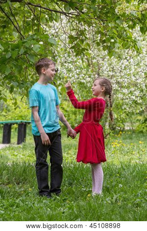 Boy and girl walking in the park and a girl gives a flower boy.