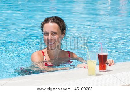 Woman swimming in the pool with near the drinks.